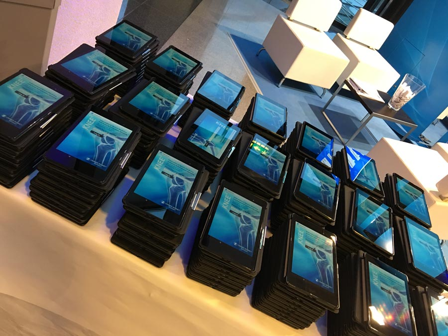 A pile of tablets running an Event App ready for use